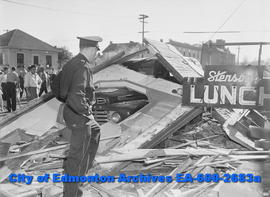 """Explosion Levels City Lunch Shop"". Officer inspects scene."