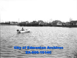 Boatbuilder Frank Barrigan using his boat to travel through spring run-off at 109 Street and 111 ...