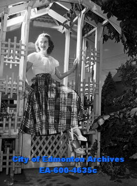Peggy Newland sitting on a gate under an arbour.