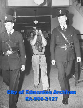 """Police Escort Accused in Slaying"". L-R: Const. Bill Fedorak, Hong Suey Chin and Const...."