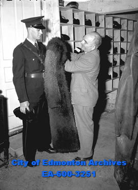 City Police issues buffalo fur coats to officers. L-R: Const. Norm Greenwell and H.S. Reynolds.