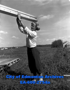 Teenagers build prefabricated cabins for YWCA. Connie Farley lifts wooden beam.