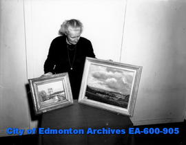 Mrs. Marjorie Pardee, general-secretary of the Edmonton Museum of Fine Arts, holds two paintings ...