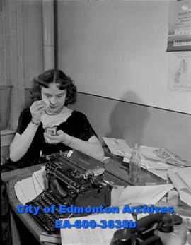 Stenographer feature: secretary applies make up at desk during working hours.