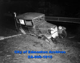 Automobile driven by Martin E. Berg dropped into a hole in front of 10137 92 Street tilting viole...