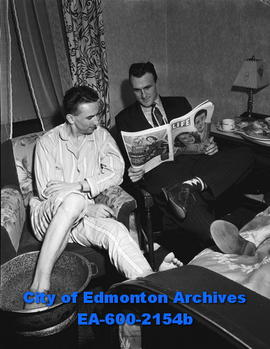 Flyers relax between games at Calgary: L-R: Bing Merluk soaks feet and Bill Maher reads.