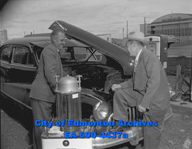 Alaskan Motors Garage: E.B. Olson (left) and L.J. Price check out engine.