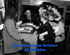 Travelling library at Glenora School: driver-director Jack Fearon surrounded by school students.