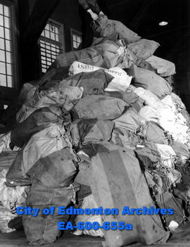 J. C. Murray on top of a pile of Christmas parcels ready to be sorted at HMCS Nonsuch's drill hal...