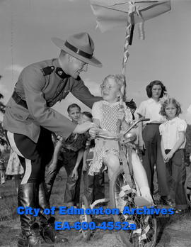Borden playground opening. RCMP Const. Scott with child on bicycle.