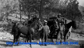 Men holding horses standing near the Charles O. Bowen's Gospel Van.