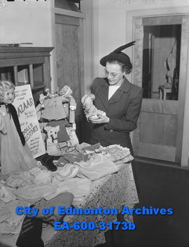 Women's Page: Mrs. N. E. Alexander prepares for Nurses' Alumni Association Bazaar.
