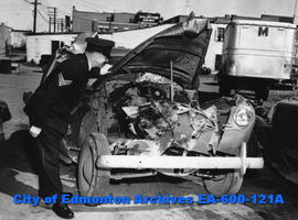 Sgt. Albert E. Woodwards, Edmonton City Police, inspecting wrecked automobile.