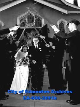 Fireman's wedding: George Waddell and Lillian Young pass arch formed by axes.