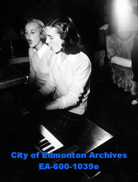 Miss Edmonton of 1948, Joan Farley, playing the piano and singing with her sister Connie.