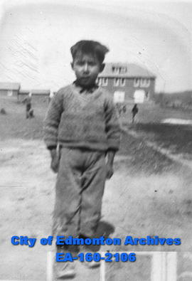 A boy near a house, possibly at a residential school.