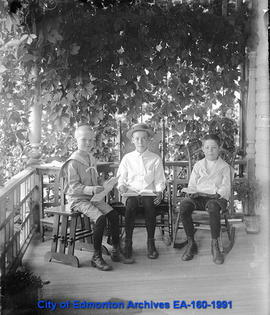 Three boys on a porch reading.