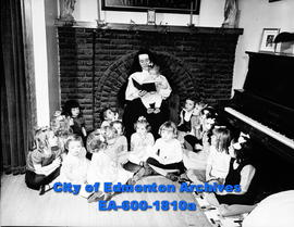 Women's Page: Sister Good Counsel reads to children at O'Connell Institute before going to bed.