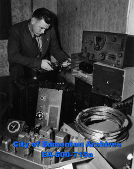 Constable Alfred Edwardson looks over stolen radio equipment found in the garage of a 17-year-old...