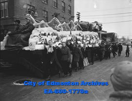 Christmas parade sponsored by T. Eaton Company; children crowd around Santa Claus float.