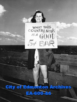 Jean Biglow holding sign protesting eight cent chocolate bars, Edmonton