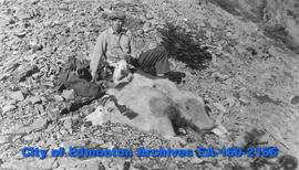 A hunter sitting besides his kill of two mountain goats.