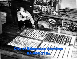 """Eggman,"" collector of eggs and butterflies, with trays of eggs."