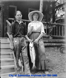 A man and woman in front of a cabin holding a fish.