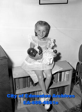 Young girl holding doll, sitting on bookcase.