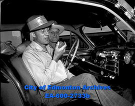 Yellowhead route car caravan. Wilson Faulder and Ed Olson test communications equipment in radio ...
