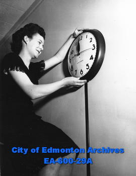 Vera Croucher adjusting clock, daylight savings time promotion.