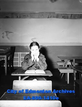 Youngsters back to school for fall; girl sitting at school desk.