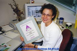 Editor Lori Yanish accepts the Apex certificate on behalf of the corporate team