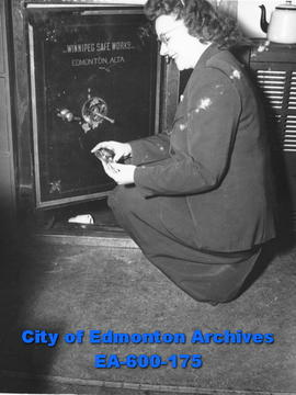 Eileen Hutchinson, employee of the Arctic Ice Company, examining damaged safe, Edmonton.
