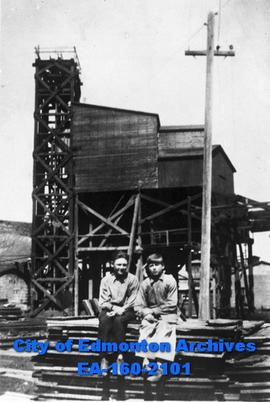 Two boys in front of a mill.