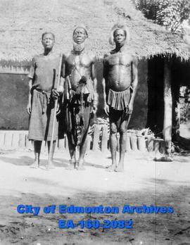 Three African Men in front of a house (hut).