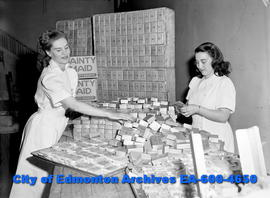 Bakery workers, Bertha Jacobson and Bertha Shecter wrap birthday cake for Calgary's 75th birthday...