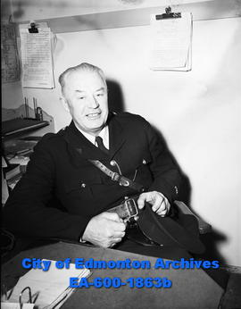 "Const. J.G. ""Jim"" Miles at his desk."