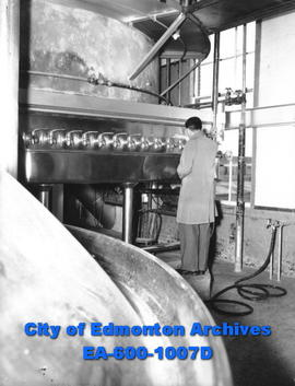 Northwest Breweries: man examining brewing machine.