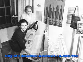 Mrs. J. R. MacRae, seated at loom, and Mrs. Jack Hutton, examining weaving, members of the Mary S...