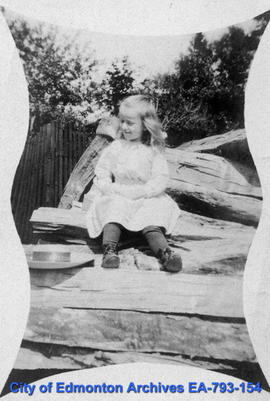 Girl sitting on woodpile