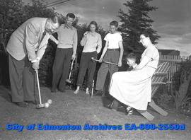 Women's Page:  Herbert E. Hamly plays croquet with family. L-R: Herbert E. Hamly with Donald, Don...