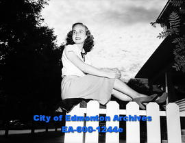 Woman posing on picket fence.
