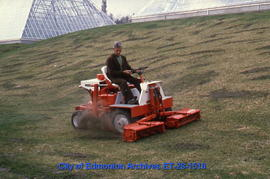 Employee on riding mower at Muttart Conservatory