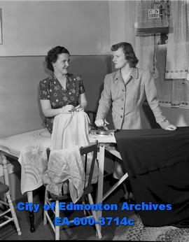 Women's Page: Girls of Beta Sigma Phi. Shirley Bredehoft and Ida Cunliffe iron clothes.