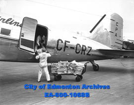 The Edmonton Bulletin, air edition, being loaded by Eric Erickson (in plane) and Ken Symington in...