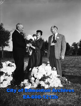 Charles H. Grant, AMA branch president, presents flowers to L.E. Shields as C.V. Cunningham, chai...