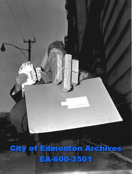 Mailman D.P. Ramsay with arms full of parcels.