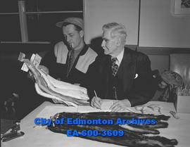Alberta Fur Breeders' Association exhibition. A.G. Walker and Terry Langhodge inspect pelts.