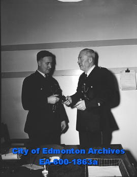 "Const. J.G. ""Jim"" Miles retiring. Const. J.H. McCallum accepts his badge and gun."